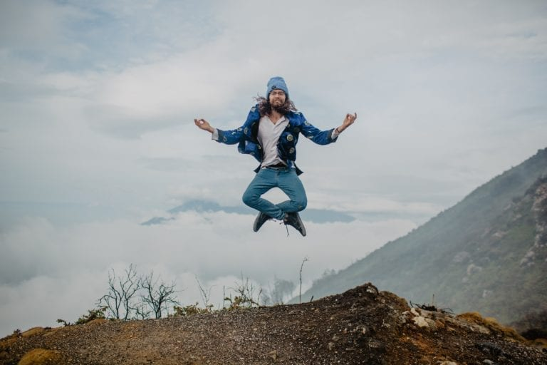 man-jumping-on-mountain-plateau-against-cloudy-sky-4553379-scaled